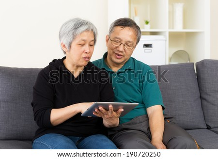 Senior couple with touchpad sitting at home - stock photo