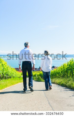 Senior couple, woman and man, having walk in vineyard