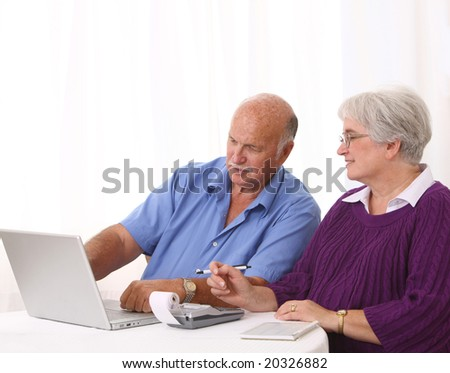 Senior couple working on finances - stock photo