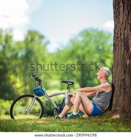 Senior cyclist sitting by a tree in a park with a water bottle in his hand and listening to music on headphones shot with tilt and shift lens - stock photo