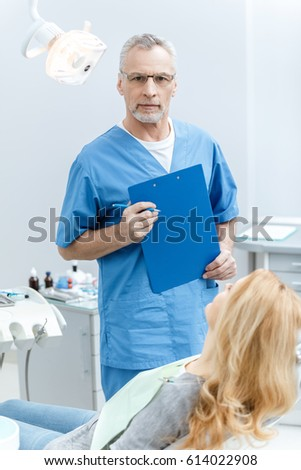senior dentist holding folder in uniform with patient in dental clinic