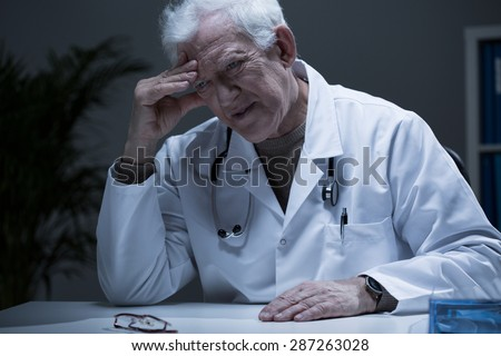 Senior depressed doctor worried about his life - stock photo