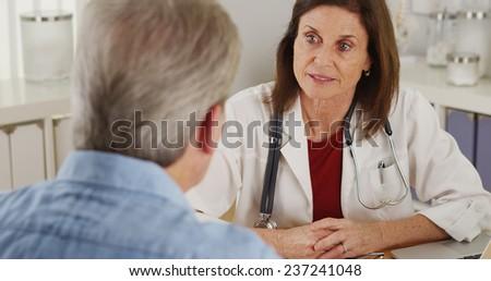 Senior doctor advising elderly patient - stock photo