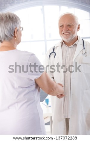 Senior doctor and female patient shaking hands.