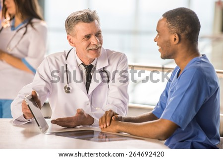 Senior doctor and young doctor talking and using a tablet. - stock photo