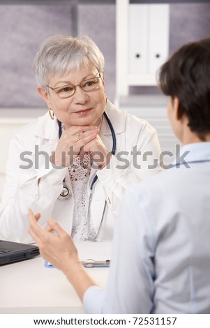 Senior doctor listening to patient in office, smiling.? - stock photo