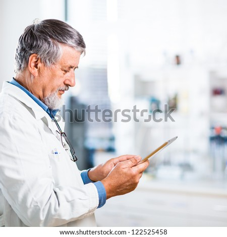Senior doctor/scientist using his tablet computer at work (color toned image) - stock photo
