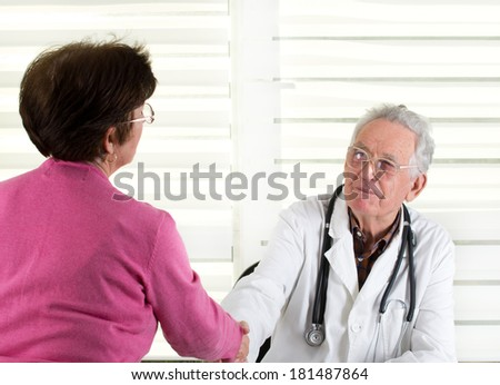 Senior doctor shaking hands with older female patient - stock photo