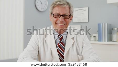 Senior doctor sitting at desk smiling at camera - stock photo