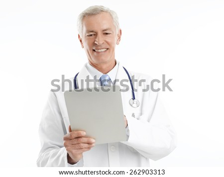 Senior doctor standing at hospital and using a digital tablet for his diagnosis. Isolated on white background.