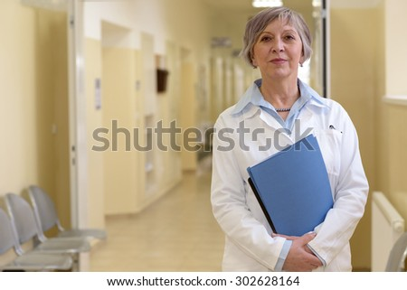 Senior doctor standing in hospital hallway holdings patient files