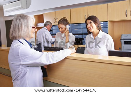 Senior doctor talking with receptionist at hospital reception - stock photo