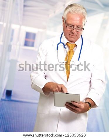 Senior Doctor Using Digital Tablet, Indoors - stock photo