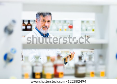 Senior doctor using his tablet computer at work (color toned image) - stock photo