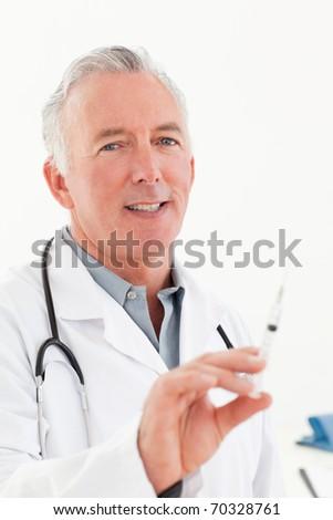 Senior doctor with syringes - stock photo