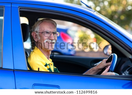 Senior driver driving a blue car looking happy