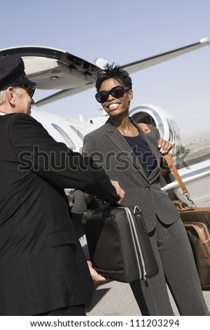Senior driver taking briefcase from businesswoman with airplane in the background at airfield - stock photo