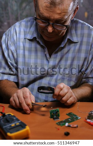 Senior electrician checking chips with magnifier and tweezers. Male engineer repairing computer board.