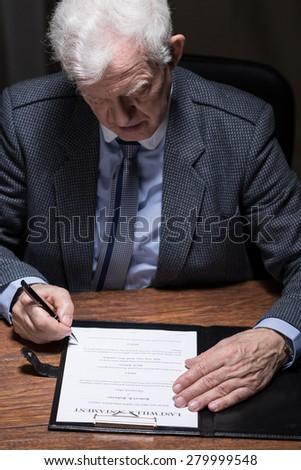 Senior elegant man signing his last will testament - stock photo