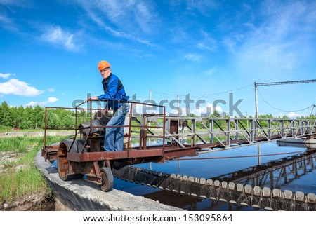 Senior engineer in hardhat standing on waste water treatment unit - stock photo