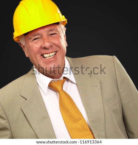 Senior Engineer Standing And Smiling On Black Background - stock photo