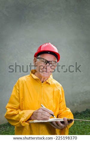 Senior engineer writing notes on building site - stock photo