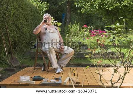 Senior enjoying beer in his garden - stock photo