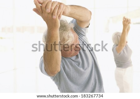 Senior exercising at gym - stock photo