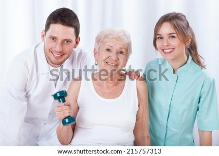 Senior exercising with dumbbell and her physiotherapist