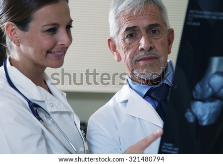 Senior expert male doctor analyzing x-ray scan with his female assistant. - stock photo