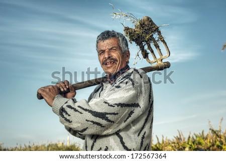 Senior Farmer holding hay fork in the fields  - stock photo