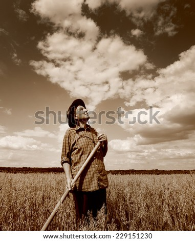 Senior farmer standing in field and looking up in the sky - stock photo