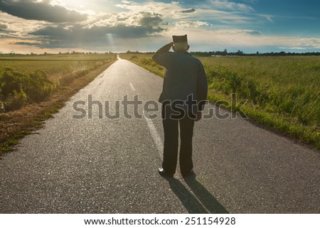Senior farmer standing in middle of the road and overlooks toward the sun on unusual sunbeam - stock photo