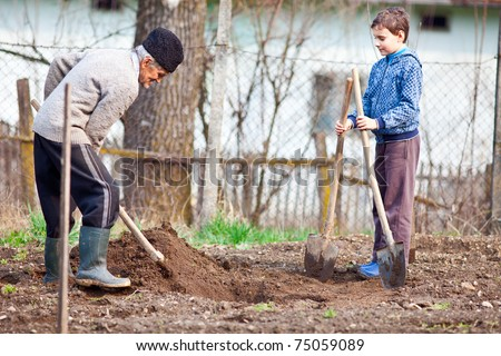 Senior farmer teaching his grandson how to plant trees in the garden