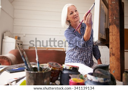 Senior Female Artist Working On Painting In Studio