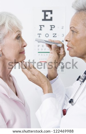 Senior female doctor checking patient's eyes - stock photo