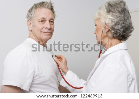 Senior female doctor checking patient using stethoscope