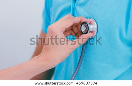 Senior female doctor checking patient using stethoscope,medical background.