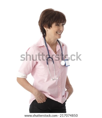 Senior female doctor smiling with hands in pockets, turning to the left. - stock photo
