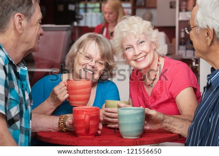Senior female friends smiling at cafe with group - stock photo