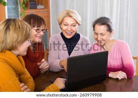 Senior female friends working with notebook using wifi - stock photo