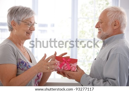 Senior female getting present from husband, smiling.?