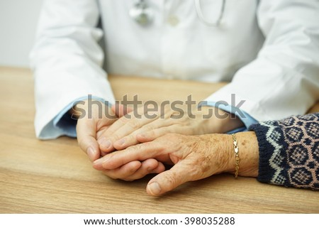 Senior female hand held by compassionate Doctor - stock photo