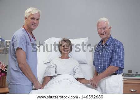 Senior female patient and husband with doctor in hospital room