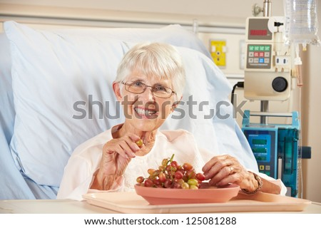 Senior Female Patient Eating Grapes In Hospital Bed - stock photo
