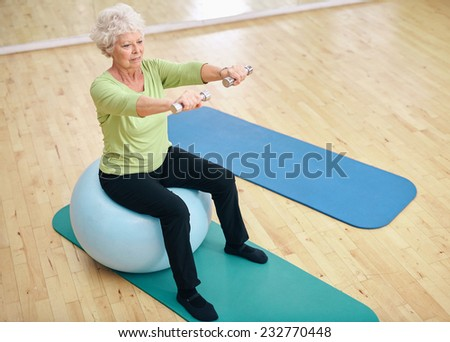 Senior female sitting on a fitness ball and lifting dumbbells. Old woman exercising with weights at gym. - stock photo
