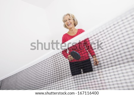 Senior female table tennis player laughing - stock photo