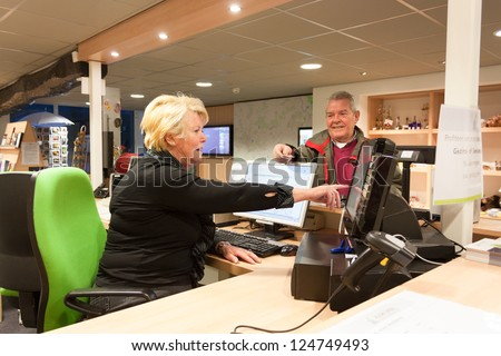 Senior female volunteer cashier selling museum ticket to Senior man at front desk