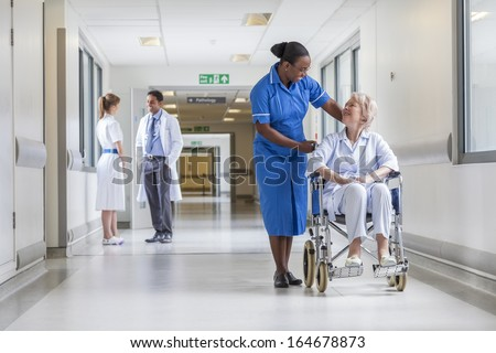 Senior female woman patient in wheelchair sitting in hospital corridor with African American female nurse doctor and nurse in background