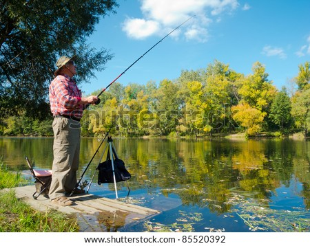 Senior fisherman catches a fish in the river at the bait - stock photo